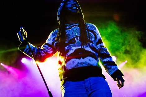 Rapper DRAM holds the microphone as colored lights set the background.