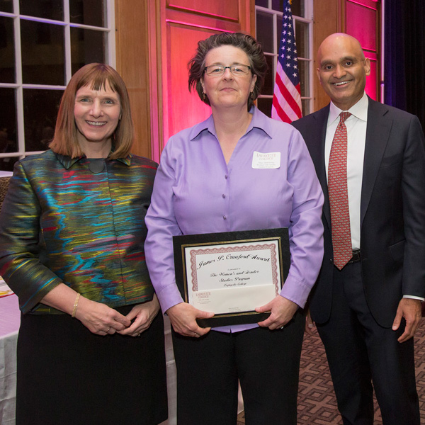 Mary Armstrong, head of the women's and gender studies program, holds her award plaque next to Alison Byerly and Abu Rizvi