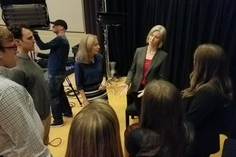 Members of the Open for Debate broadcast team stand and talk at the PBS studio.