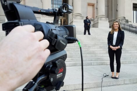 A student stands on outside steps while being filmed for the Open for Debate broadcast