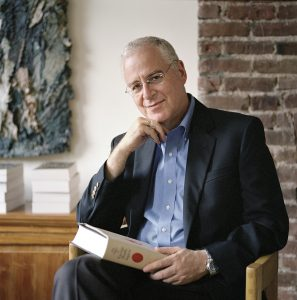 Ron Chernow holds a book on his lap while seated.