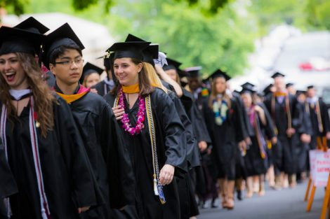 Students wearing their caps and gowns stand in line on the way to Commencement.