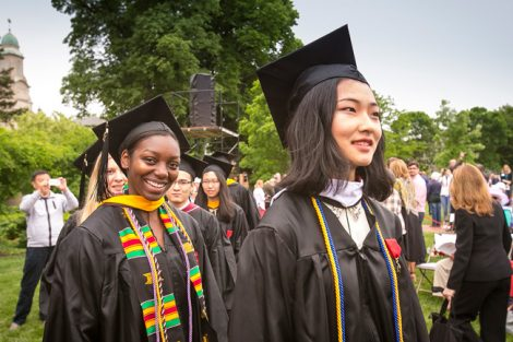 Two students smile as they walk at Commencement.