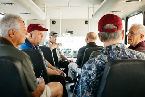 Alumni ride on a bus.