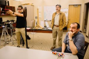 Noah Steinberg '17 shoots with his laser gun while professors Luis Schettino and Alex Brown watch.