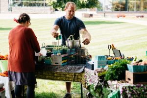 A student worker and the farm manager set up the LaFarm Marquis Market.