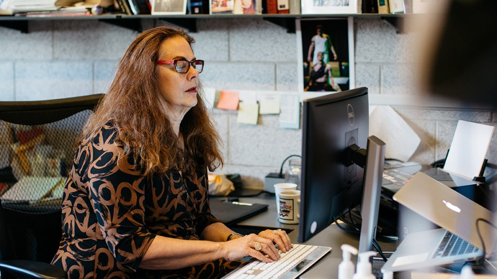 Suzanne Westfall works at a desktop computer in her office.