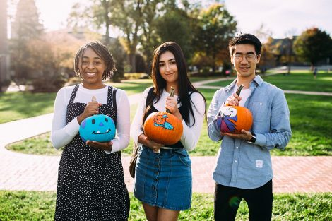 3 students hold pumpkins.