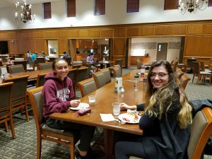 Two women students smile for a photo while sitting at a table for breakfast at Marquis Hall.