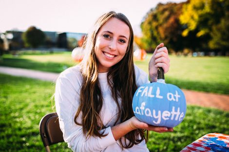 A student holds a pumpkin with the words