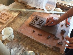 The artist forms letters on a pottery plaque.