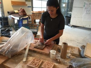Samantha Pastron '18 makes letters for a pottery plaque.