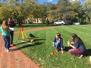 Four students conduct surveying on the Quad.