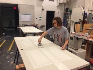 Eve Lavitz '21 works on a door to be used in the play The Drowsy Chaperone.