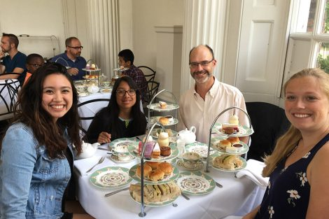 Professor Chris Ruebeck and three students at a restaurant lunch table