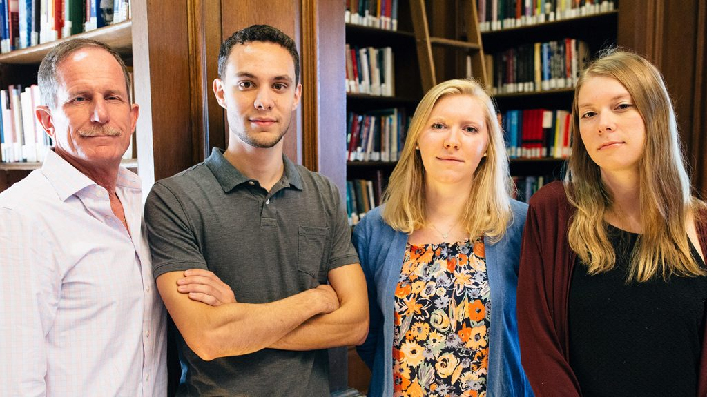 David Woglom and three students stand in front of book shelves.