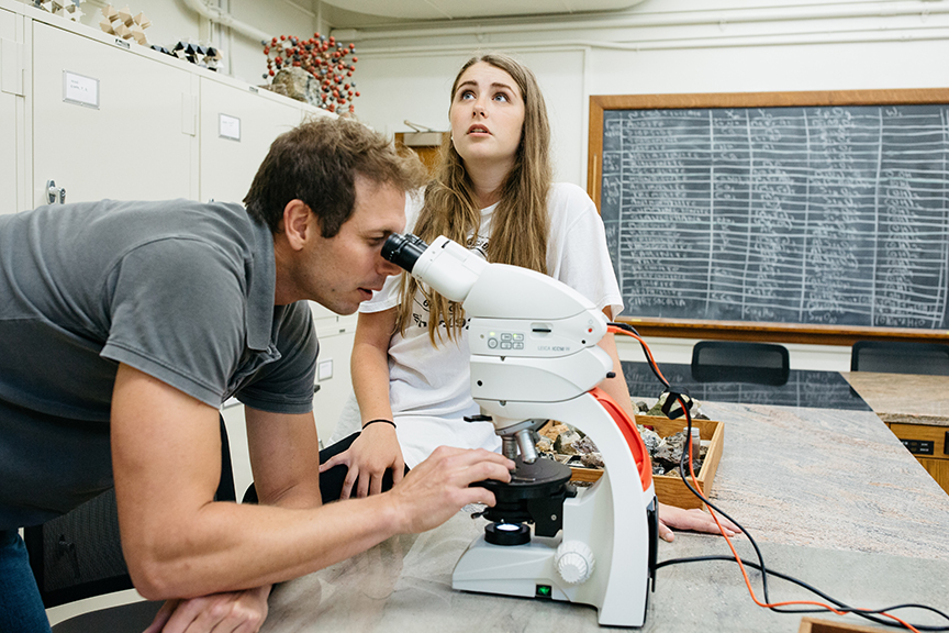 Professor Dave Sunderlin looks through a microscope as Justine Perrotti '19 looks up at the projection screen.