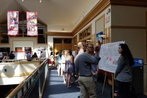 Professor Chris Ruebeck discusses two students' research poster with them.