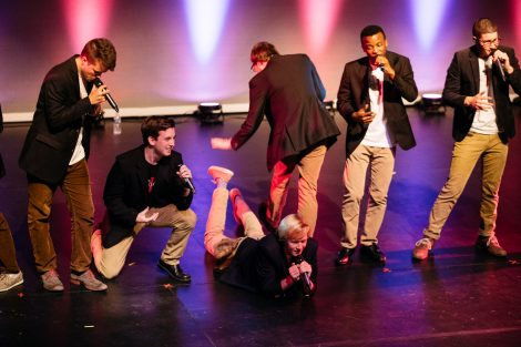 Student a cappella singers perform on stage.