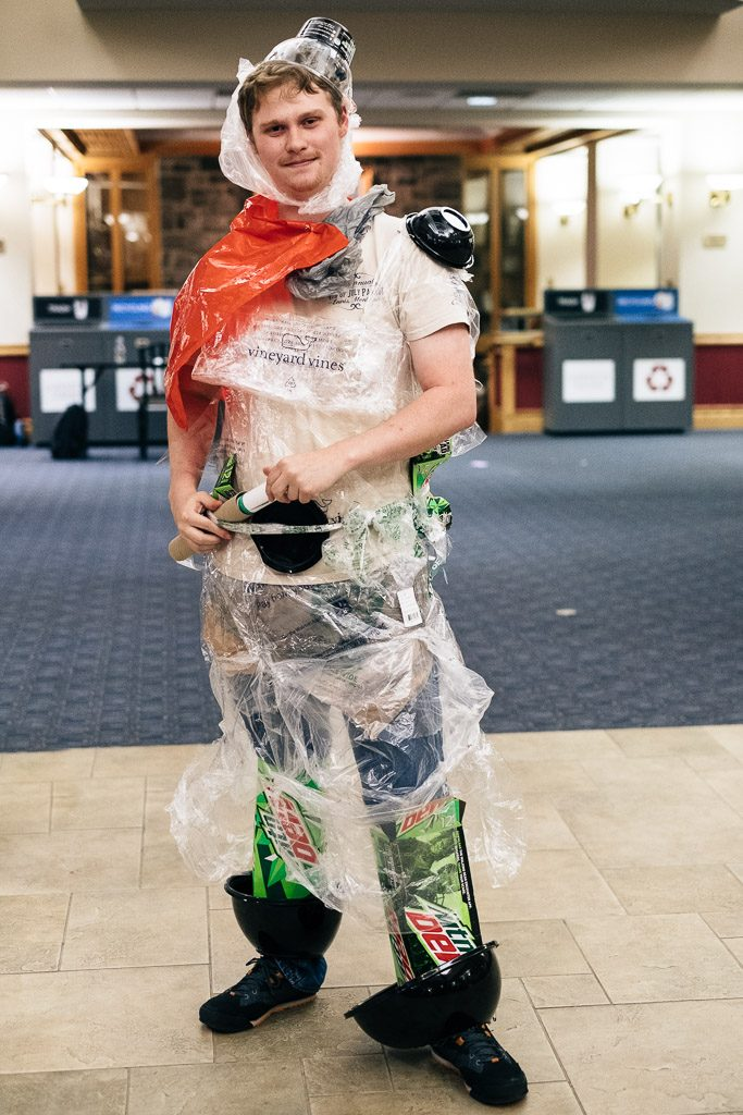 A male student wears a costume made from recycled materials.