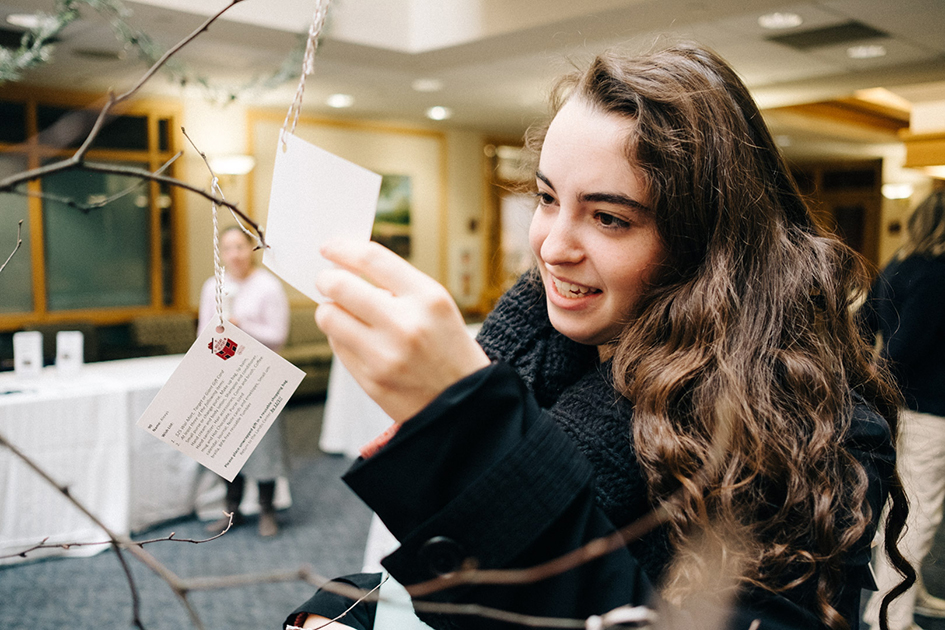 A female student examines a gift tag on the birch tree.