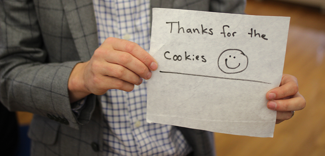 "Someone holds up a piece of paper that says ""Thanks for the cookies."""