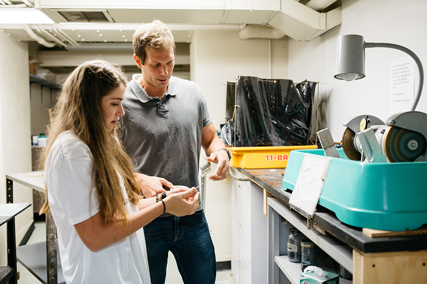Professor Dave Sunderlin and Justine Perrotti '19 look at a slide of petrified wood in the lab.