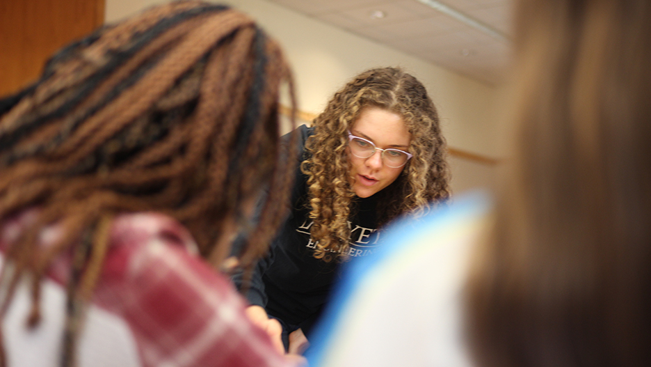 Lafayette student Sara Mikovic helps elementary school students with their project.