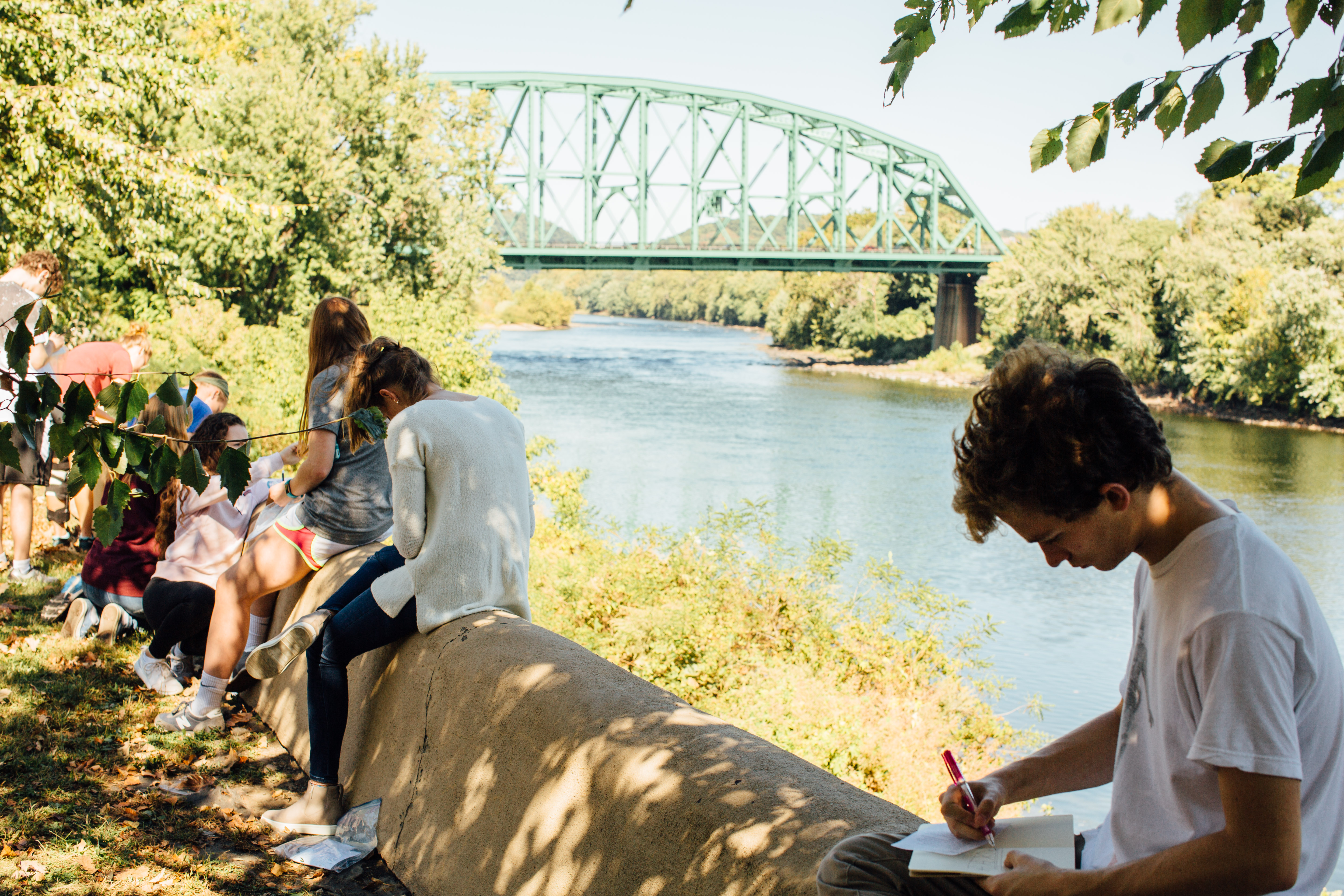 Students sketch a bridge outdoors while observing it.