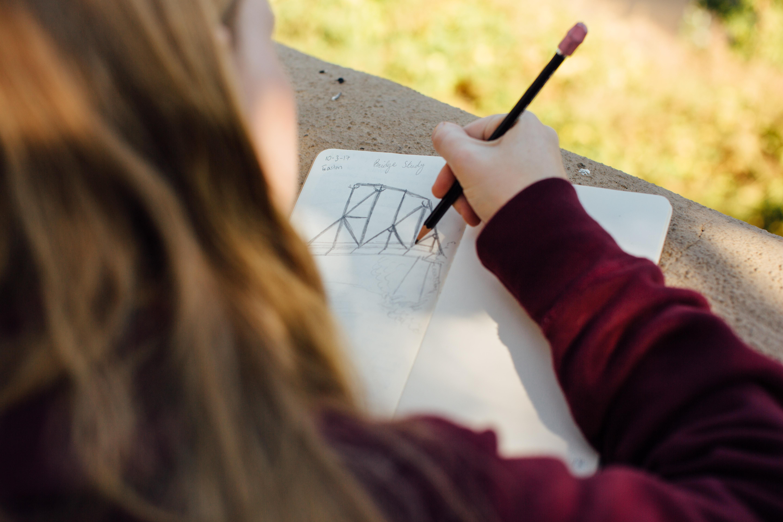 A female student sketches a bridge.