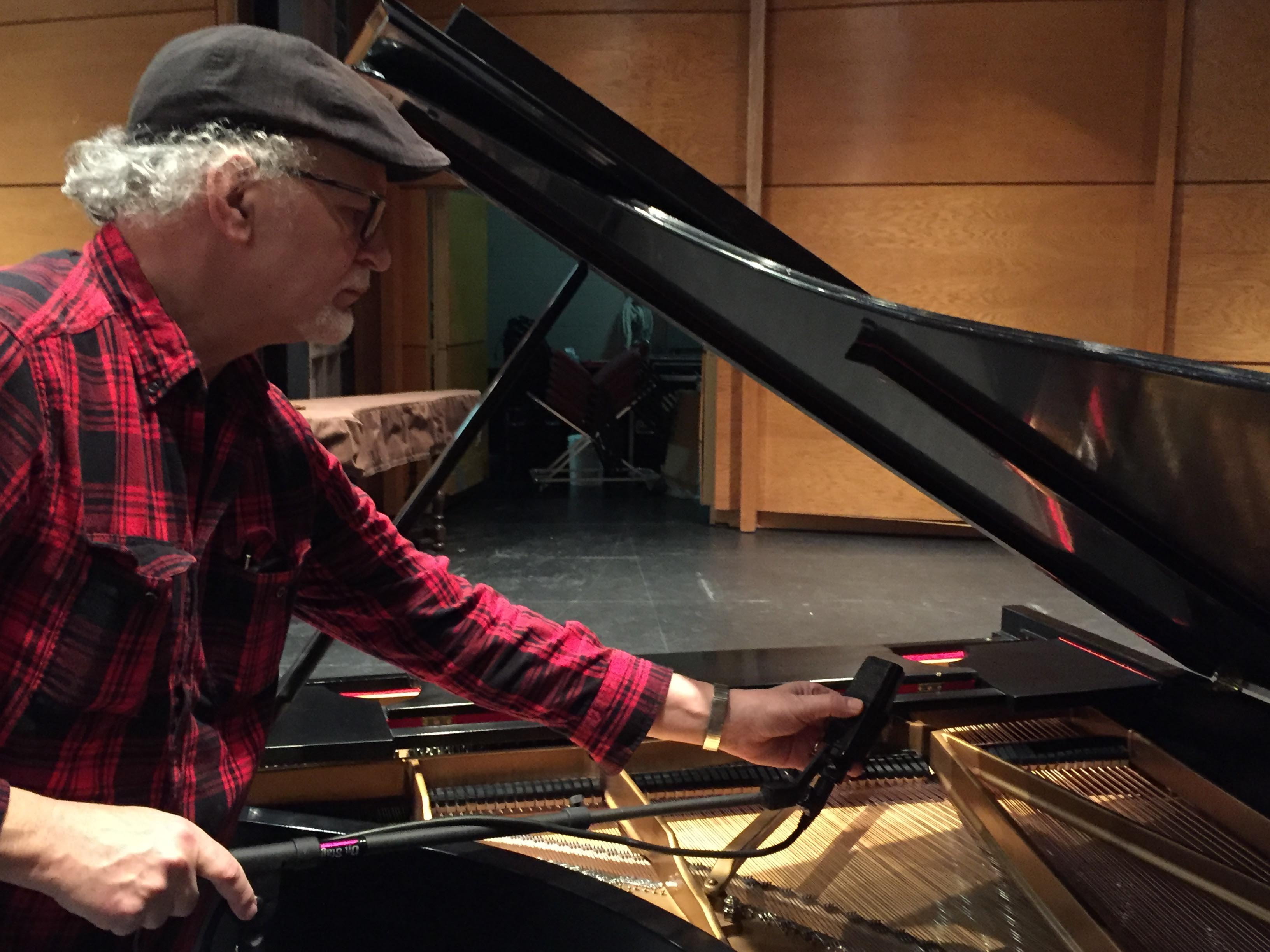 Tim Frey sets up a microphone for a piano.
