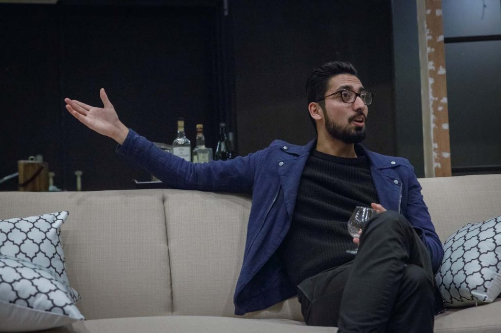 An actor in the play Disgraced talks while sitting on a couch.