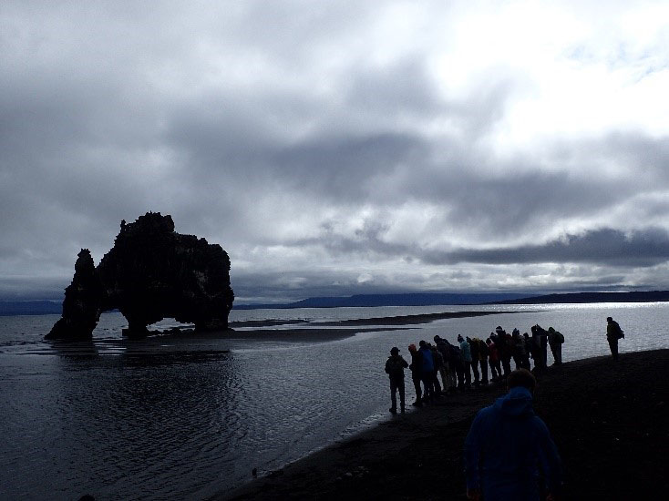 Students visit Hvitserkur, a 49-foot-tall cliff that juts out of the Atlantic Ocean.