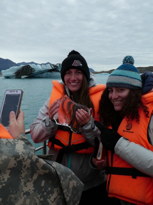 Two students with one holiding a piece of ice at Jökulsárlón Glacier Lagoon in Iceland.