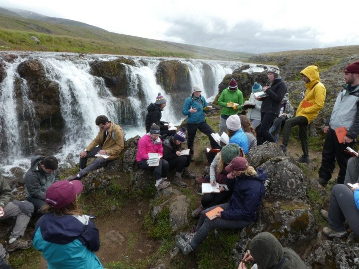 Students have a discussion by the Kolugljúfur waterfall in northern Iceland.