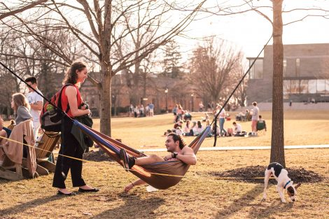 A student in a hammock is among the people on the Quad.