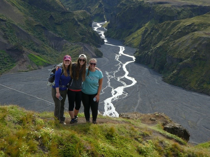 Rebecca Webster '19, Paige Santelli '19, and Kristen Ingraham '19 at the top of a steep climb at Thorsmork in southern Iceland with a high-energy river behind them
