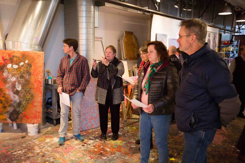 Biology faculty look at paintings in Ed Kerns' studio.