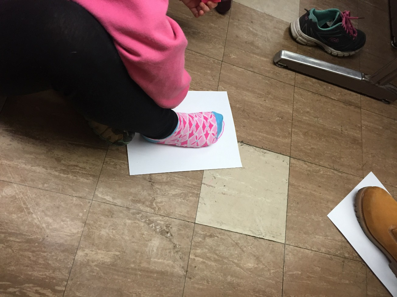 A student puts her foot on a piece of blank paper as part of a lesson on climate change at Cheston Elementary School.