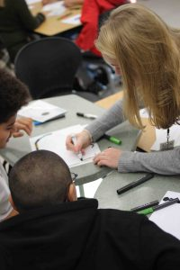 A Lafayette student works on a piece of paper while young pupils watch.