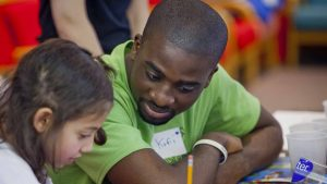 Kofi Boateng sits with a child who is writing during Literacy Day at Lafayette.