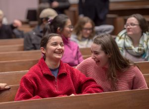Two students laugh as Laila Lalami, author of this year's Community Reading, Hope and Other Dangerous Pursuits, speaks at Colton Chapel.