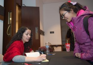 Laila Lalami, author of this year's Community Reading, Hope and Other Dangerous Pursuits, signs a copy of her book for a student after her lecture at Colton Chapel.