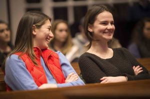 Two women students smile during the Keith Whittington lecture.