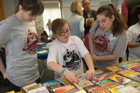 Students work with elementary school children during the Literacy Day event in the Marlo Room of Farinon.