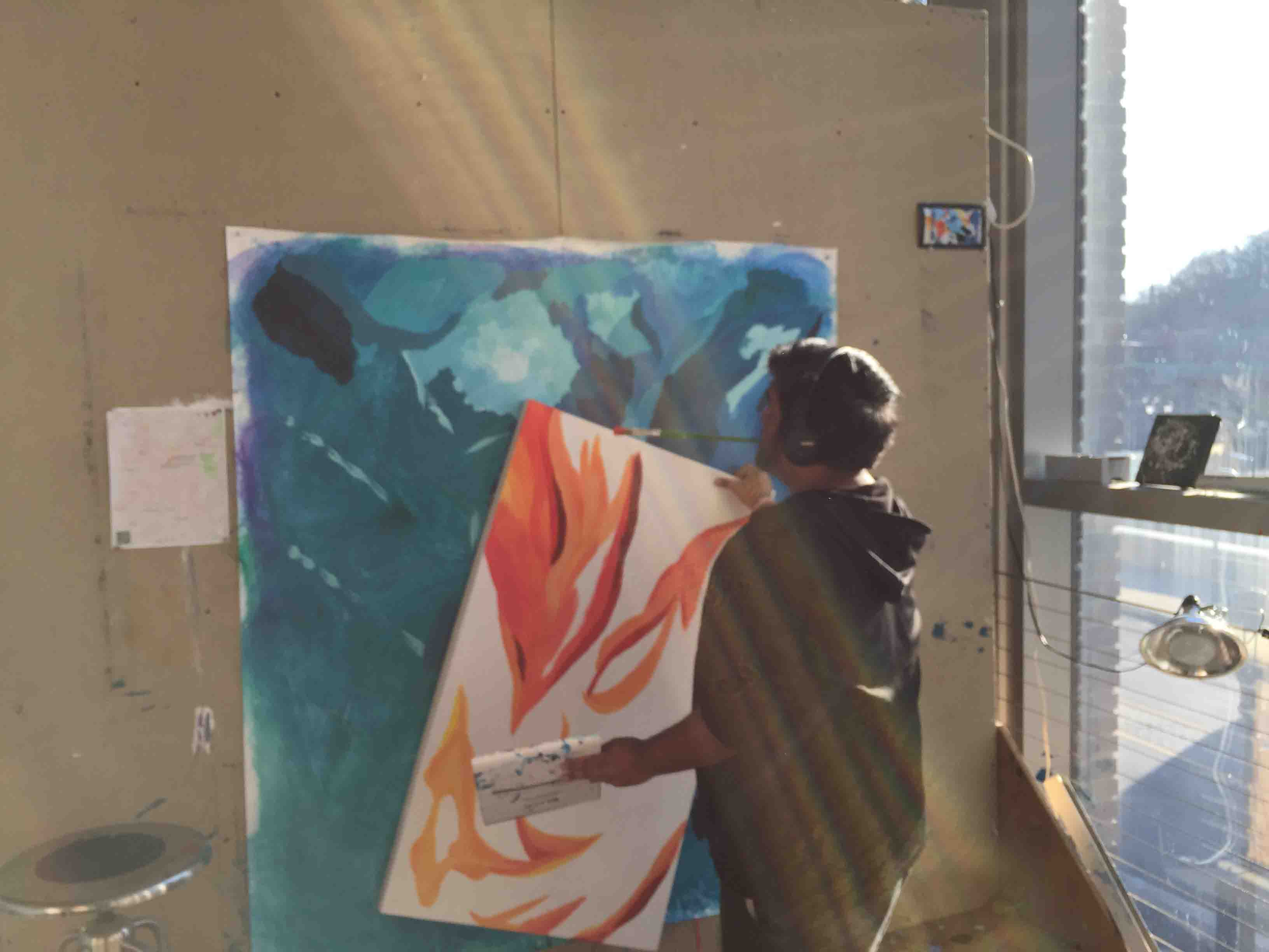 Pablo Pollish '18 moves one of his paintings on canvas in the Williams Visual Arts Building.
