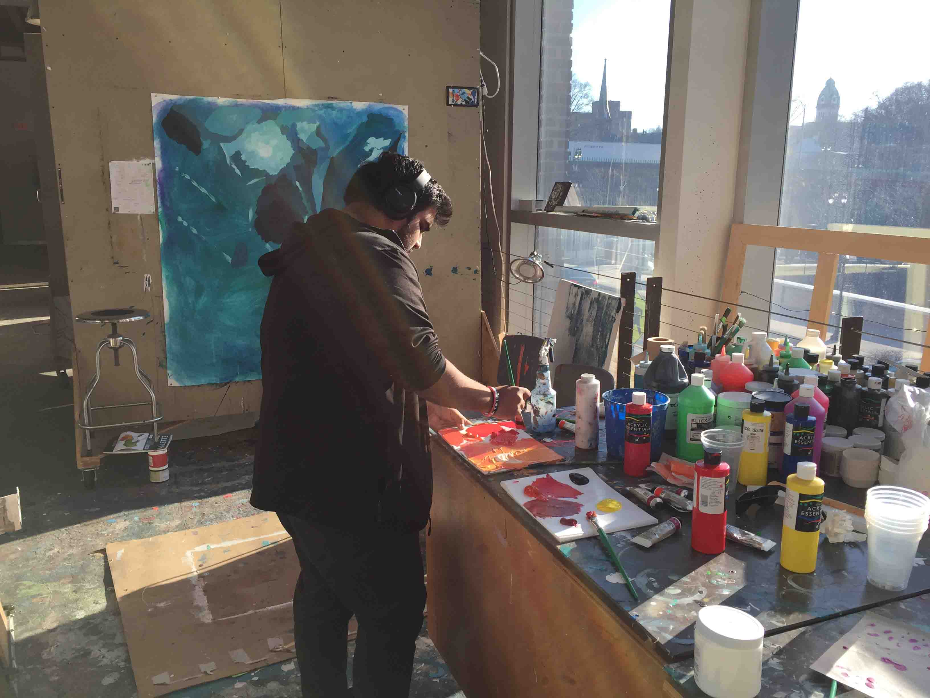 Pablo Pollish '18 paints on canvas in the Williams Visual Arts Building.