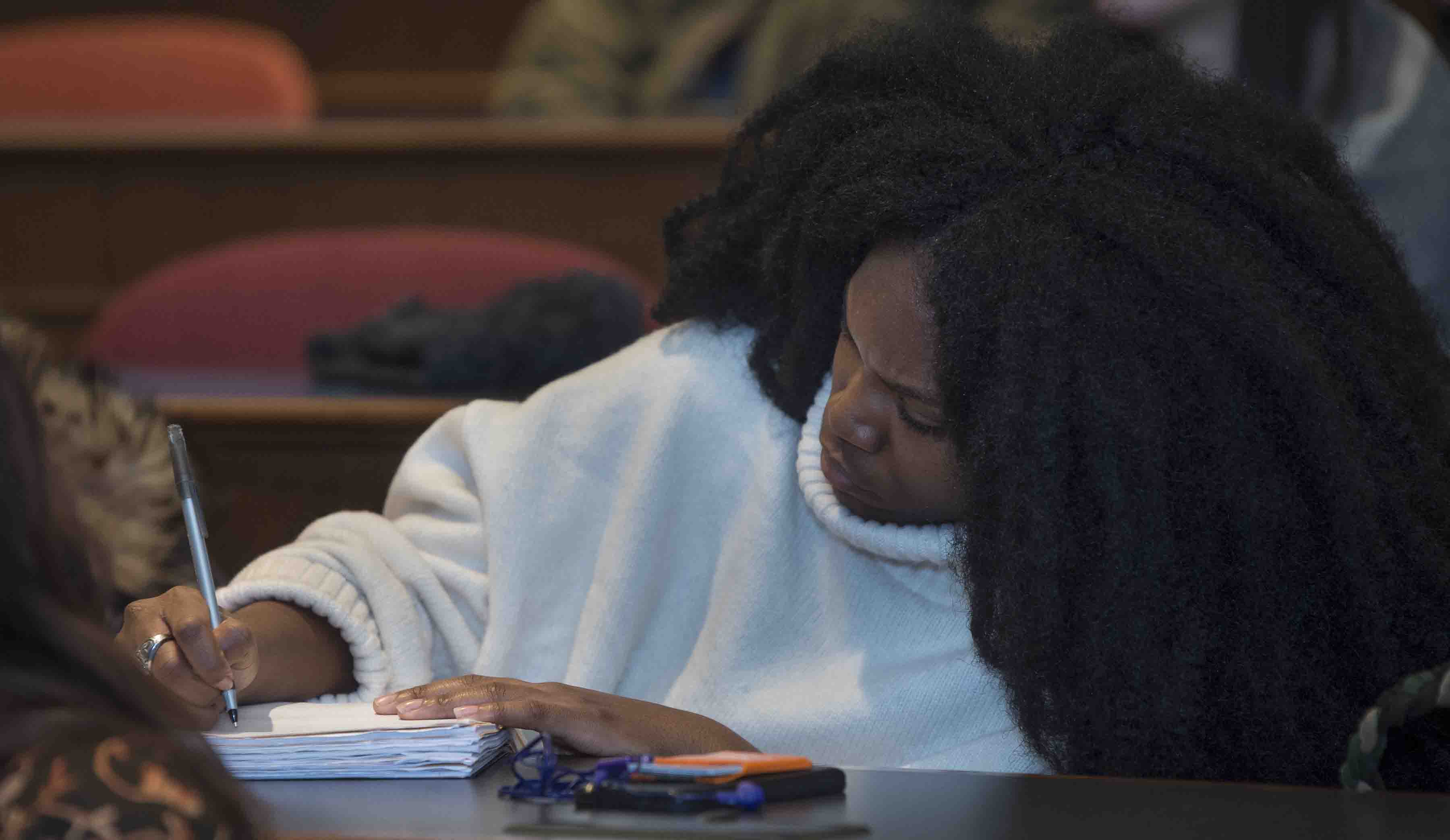 A student takes notes on Kevin Young's lecture on fake news.
