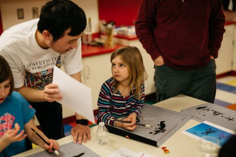 A Lafayette student teaches a child how to do a craft project.