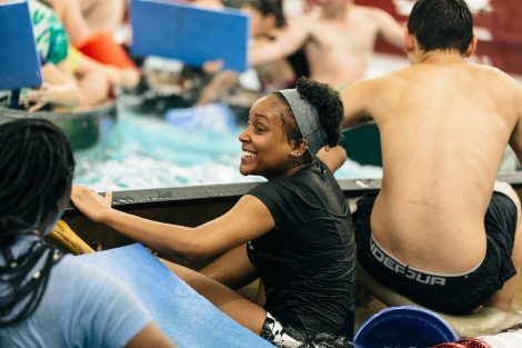 Students try to flood and sink other canoes in the Battleship game in Weinstein Natatorium.